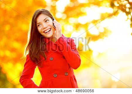 Smart phone Autumn woman talking on mobile phone in fall. Autumn girl having smartphone conversation in sun flare foliage. Portrait of mixed race Asian Caucasian young woman in forest in fall colors.