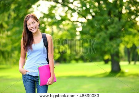 Student girl portrait holding books wearing backpack outdoor in park smiling happy going back to school. Asian female college or university student. Mixed race Asian / Caucasian young woman model.