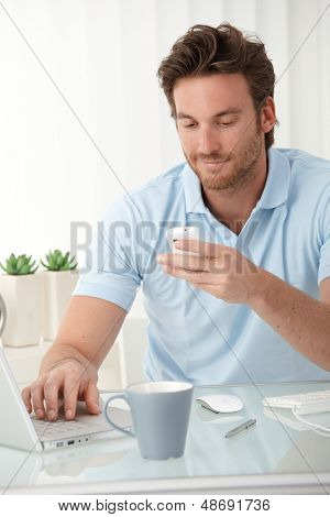 Smiling man using mobile phone for texting, typing on laptop computer, sitting at desk.