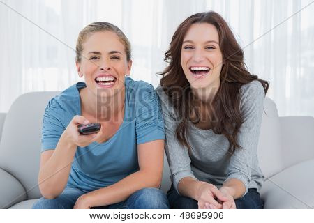 Laughing women watching television  sitting on the sofa