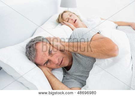 Annoyed man blocking his ears from noise of wife snoring at home in bedroom