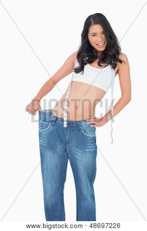 Smiling sexy woman wearing too big pants on white background