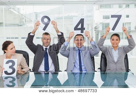 Cheerful interview panel holding signs giving marks in bright office