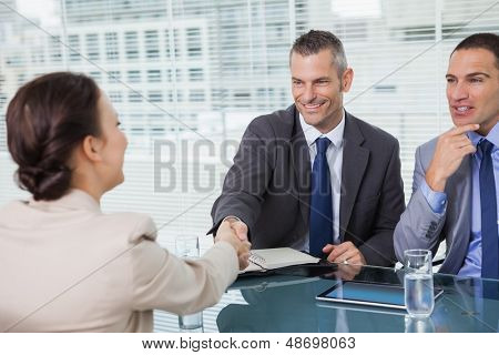 Brown haired woman shaking hands with her future employer in bright office