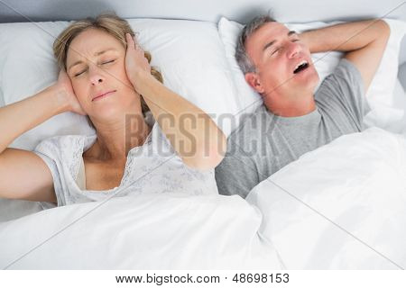 Wife blocking her ears from noise of husband snoring in bedroom at home
