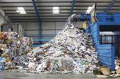 stock photo of dump  - Waste falling on pile from conveyor belt at recycling factory - JPG