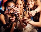 stock photo of positive  - Group of partying girls clinking flutes with sparkling wine - JPG