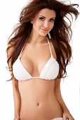 foto of curvaceous  - Charming sexy young brunette woman with large breasts and windblown hair posing in a white bikini  upper body isolated studio portrait - JPG