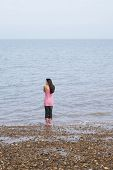 foto of herne bay beach  - Rear view of young woman standing by seaside on beach - JPG