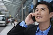 Closeup of young businessman looking up while using cell phone on street