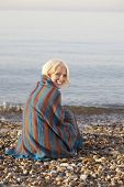 stock photo of herne bay beach  - Portrait of beautiful young woman wrapped in blanket sitting at beach - JPG