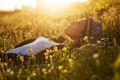 stock photo of beatitudes  - Happy girl lies among the wild flowers on a summer evening - JPG