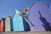 pic of herne bay beach  - Full length of young woman jumping in front of beach huts against blue sky - JPG