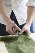 Постер, плакат: Животик молодой мужской портной резки ткани за столом в студии моды