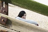 image of herne bay beach  - Happy young woman looking away while sitting behind balustrade at beach - JPG