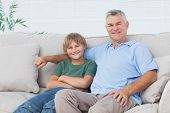Young boy sitting on the couch with grandfather in the living room