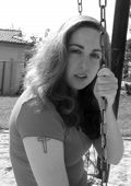 picture of swingset  - a black and white photograph of a young woman with a tattoo swinging on a swingset - JPG