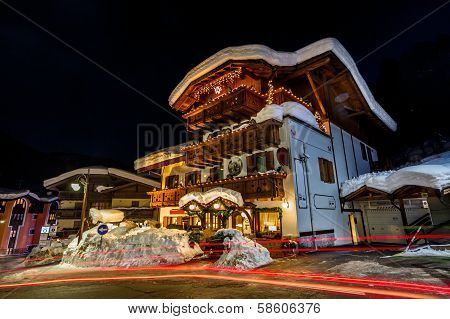 Traffic Trails On Illuminated Street Of Madonna Di Campiglio At Night, Italian Alps, Italy