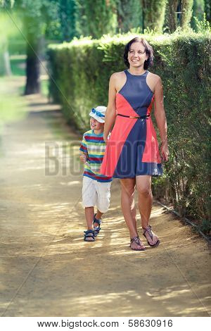 Mother and her little son walking in city park
