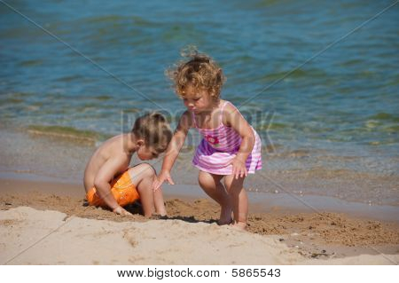 Boy And Girl Playing At The Ocean
