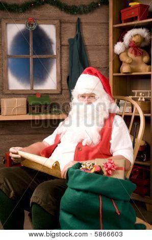 Papai Noel na cadeira de balanço com lista impertinente