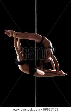 Duet of flexible young pole dancers