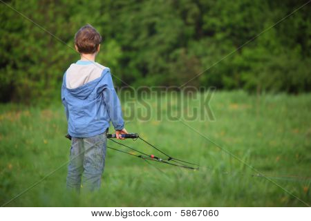 behind boy ready to kite fly on meadow