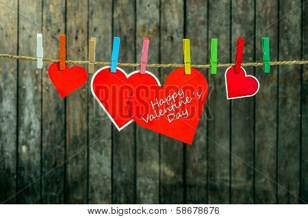 Cute big red heart hanging on the clothesline. On old wood background.