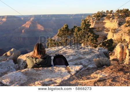 Backpacker Watching Sunrise Over Grand Canyon