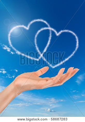 woman hand and heart shaped clouds