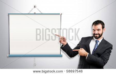 Businessman Pointing To Projector Screen Over Grey Background