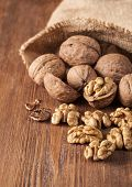 foto of walnut  - Walnut kernels and whole walnuts on rustic old wooden table - JPG