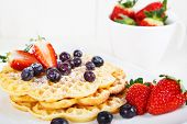 image of crisps  - Crisp golden fresh baked waffle topped with strawberries and blueberries on white table - JPG