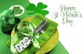 stock photo of shamrock  - Happy St Patricks Day table setting with shamrocks and leprechaun hat and sample text greeting on green and white background - JPG
