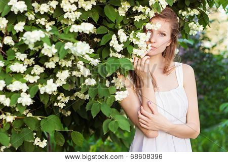 beautiful young sexy elegant girl in a white dress standing in the garden near a tree with Jasmine