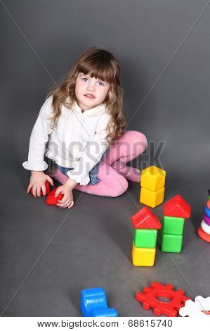 Little girl sitting on floor and builds tower of blocks