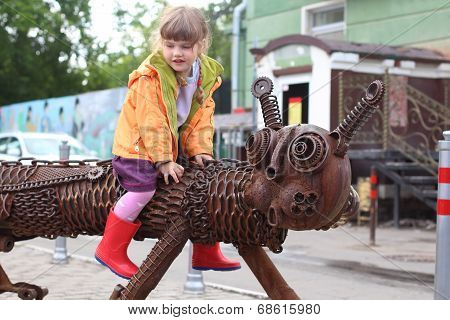 PERM RUSSIA - JUL 18 2013: Little girl sits astride city sculpture Kotofeich near Crystal cinema