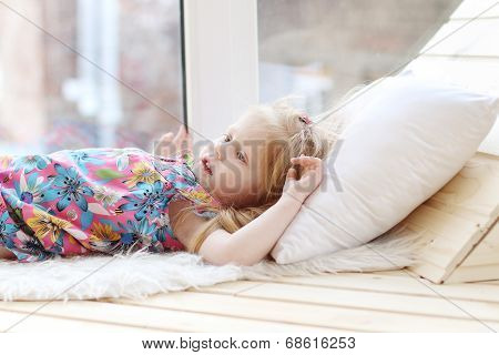 Pretty Little Blonde Girl Lies On White Pillow Near Window In Room And Looks Up