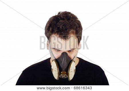 Young Handsome Man In Black Shirt And Respirator Looks Down In Studio