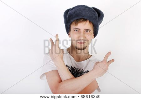 Happy Young Man In Grey Cap With Earflaps Shows Two Gesture Peace