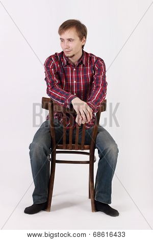 Young Man With Beard In Checkered Red Shirt Sits Astride Chair And Looks Away