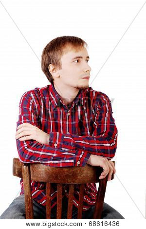Dreaming Man With Beard In Checkered Red Shirt Sits Astride Chair Isolated On White