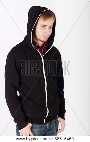 Young Sad Handsome Man In Black Hoodies And Jeans Looks Away