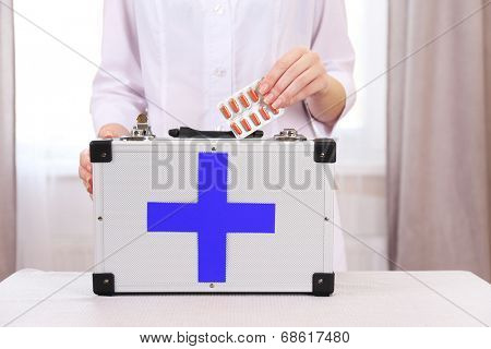 Nurse holding first aid kit in room