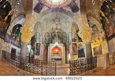 JERUSALEM, ISRAEL - MARCH 9, 2012: Ornate underground hall in the Temple of the Holy Sepulchre. Marble columns, semicircular niche - the altar, ancient paintings of biblical scenes