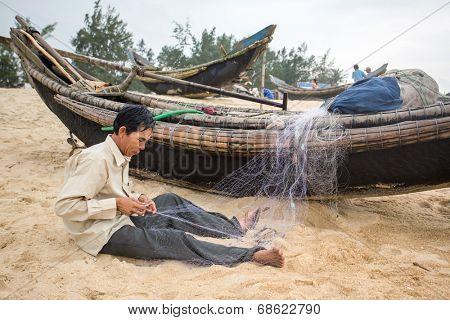 HOI AN, VIETNAM - APRIL 3, 2014: Unidentified fishermen repairing fishing nets on the beach near Hoi An, Vietnam. On April 3, 2014.
