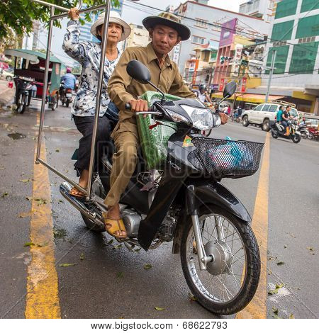 PHNOM PENH, CAMBODIA - MARCH 21: Old couple driving their motorbike in Phnom Penh, Cambodia on March 21, 2014