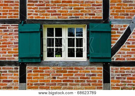 Window With Shutters In Brick Wall Of Half Timbered House