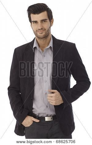 Portrait of casual businessman, jacket, hands in pocket, isolated on white, looking at camera.