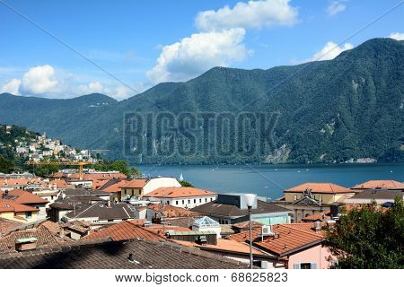 LUGANO, SWITZERLAND - JULY 5, 2014: Rooftops overlooking Lake Lugano and Alpe Trevino. The affluent city in Switzerland on the shores of Lake Lugano is surrounded by the Lugano Prealps bordering Italy